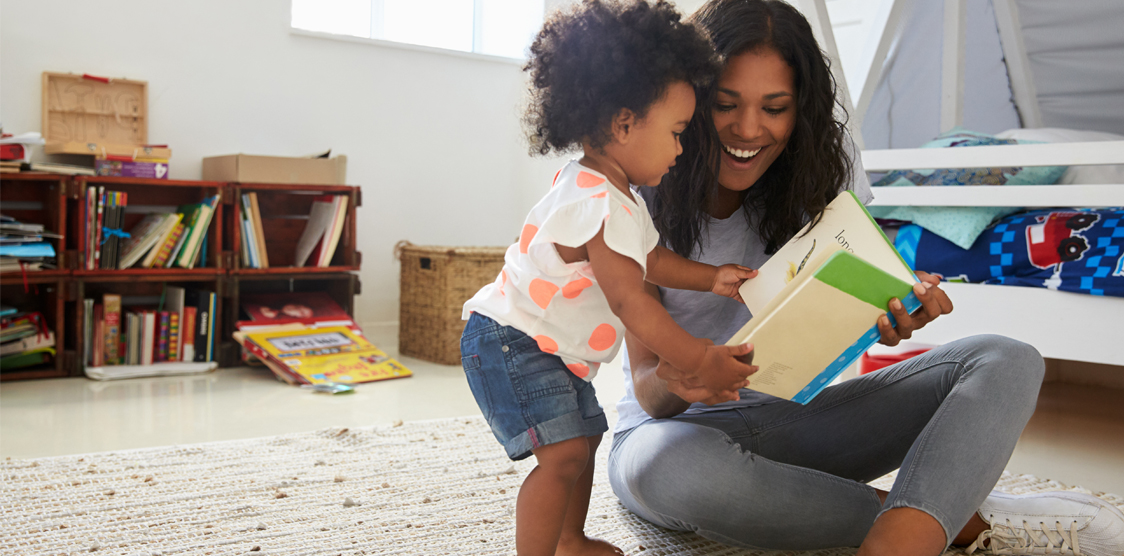 toddler reading a book with mom