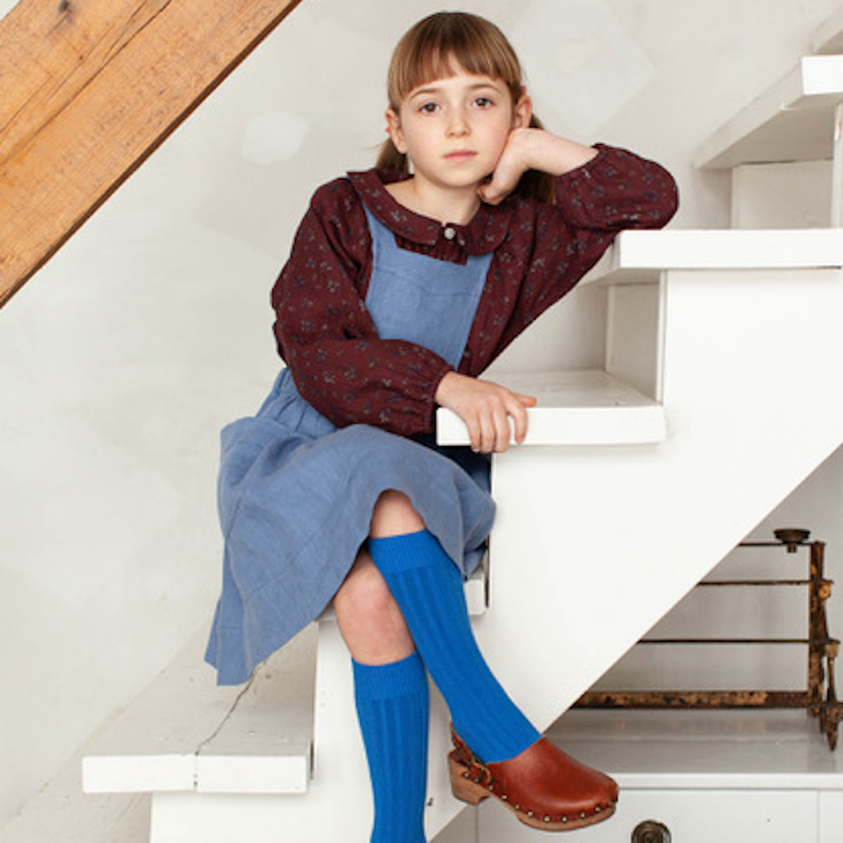 Little girl sitting on stairs wearing soor ploom clothing