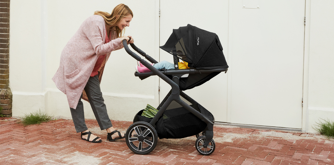 smiling mom looking into stroller at baby