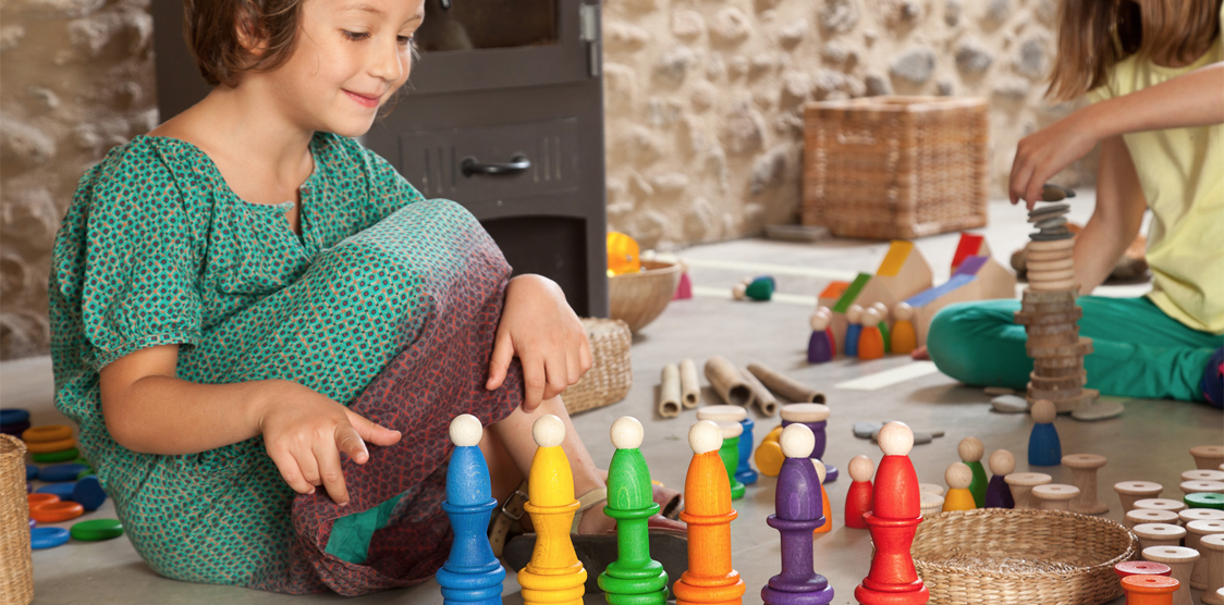 girl playing with colorful grapat wooden toys