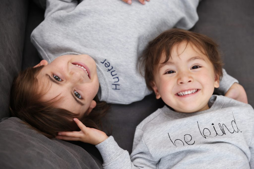 Two adorable kids wearing HART + LAND personalized sweatshirts