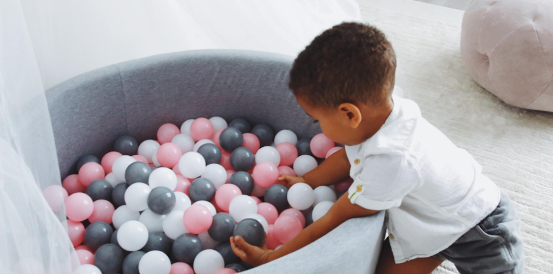 A little 2 year old boy playing in a balu organics ball pit