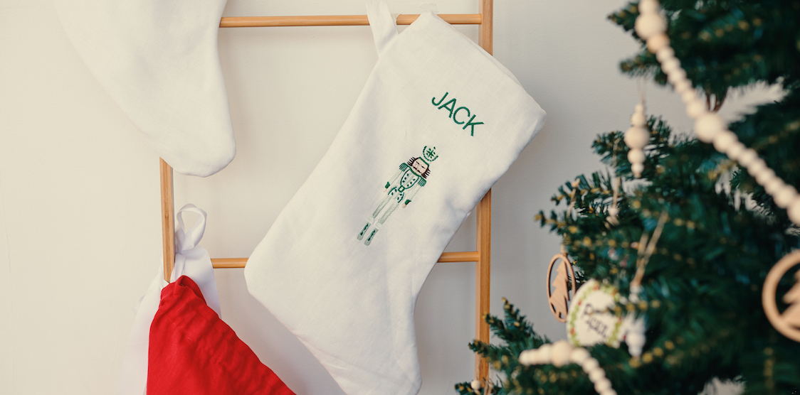 A Storybook Goods Peronsalized Stocking hanging next to a christmas tree