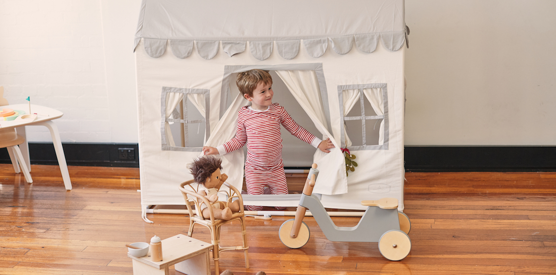 A little boy playing in a Domestic Objects indoor playhouse
