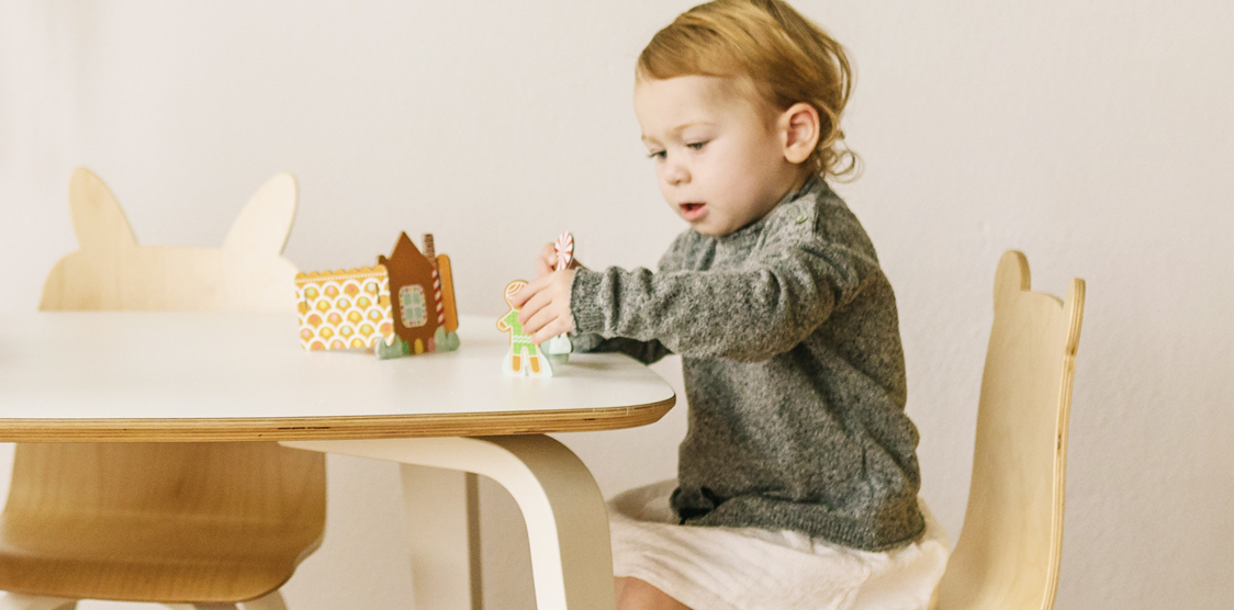 little girl playing with cardboard gingerbread house