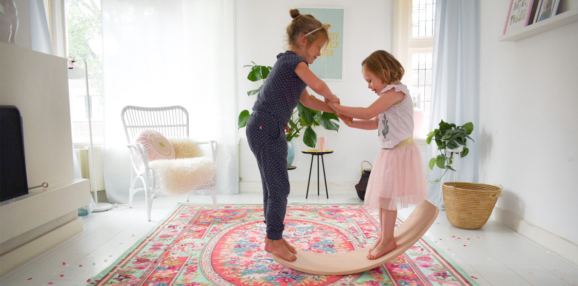 Two girls playing on the Wobbel, a balance board for kids.