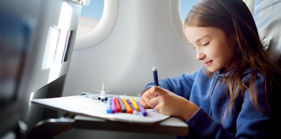 little girl coloring in on plane