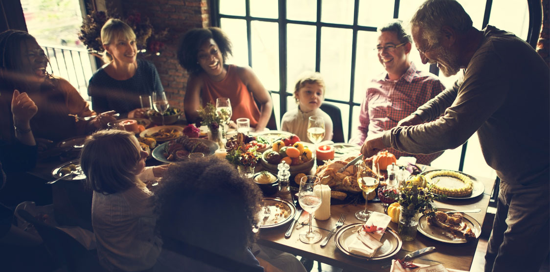 Happy people sitting around a thanksgiving table