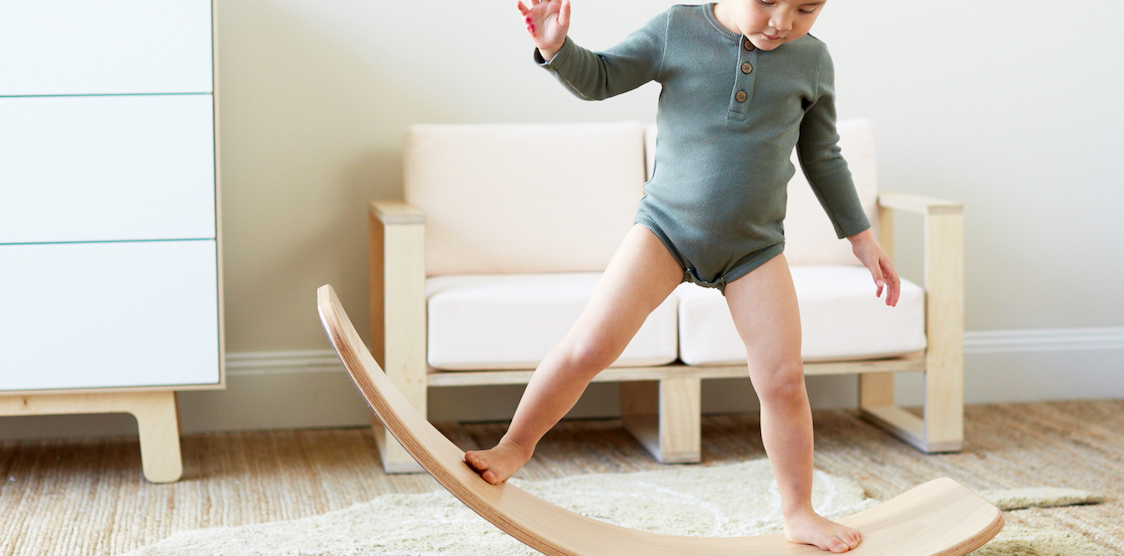 A little girl playing on the Wobbel balance board