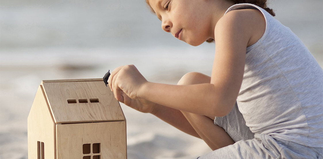 A little girl playing with a minimalist dollhouse from Babai