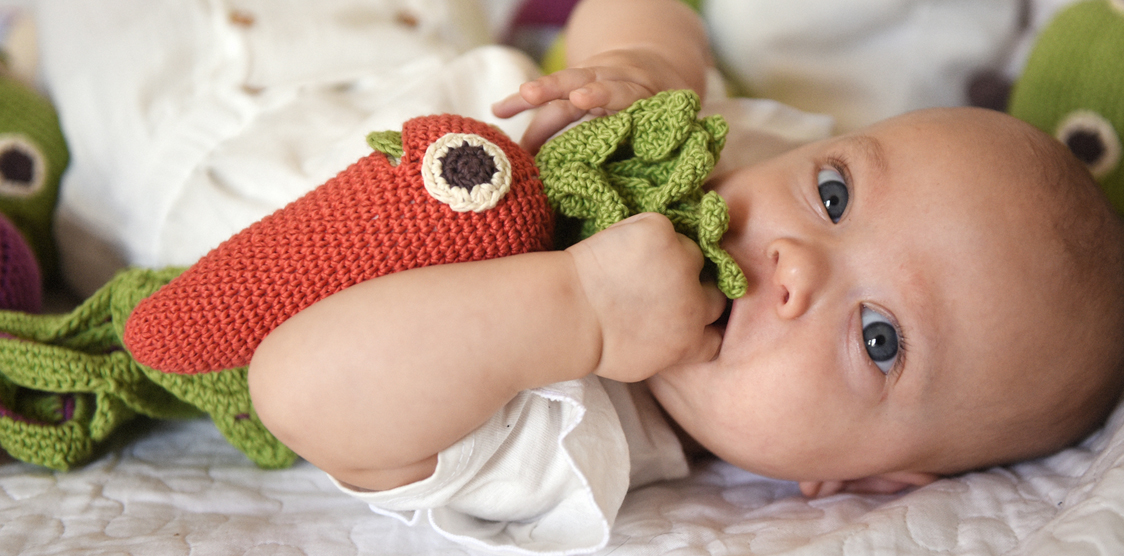 baby playing with a crochet carrot rattle toy