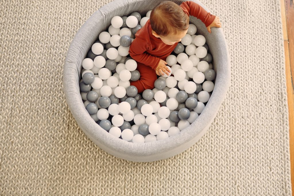 A little girl wearing HART + LAND clothing and playing in a Balu Organics Ball Pit