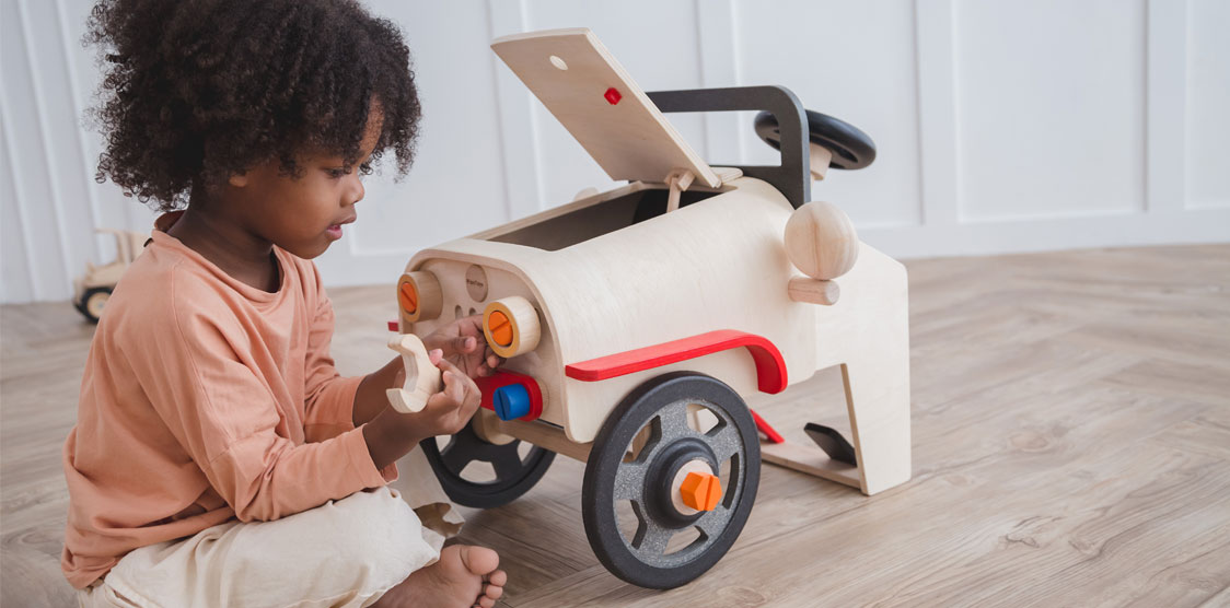 toddler playing with a wooden mechanic toy set
