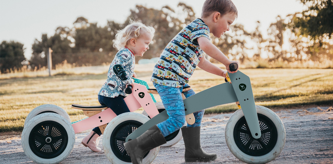 two kids riding their sustainable balance biks