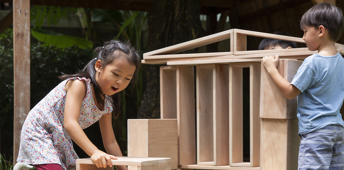 Two five year old children playing with the Guidecraft Outdoor Hollow Block Set