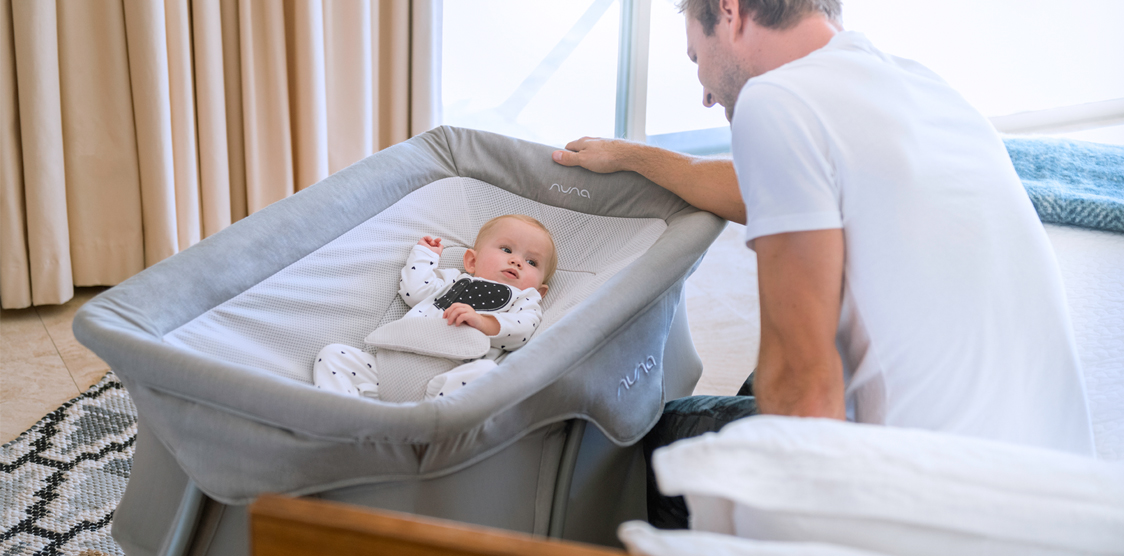 dad looking at baby in a nuna cove travel crib