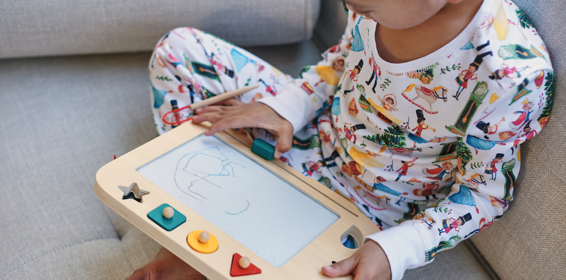 A little kid playing with the Petit Collage Doodle & Draw Elephant while wearing HART + LAND organic pima cotton pajamas