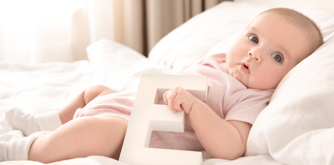Baby lying on a bed with the letter E