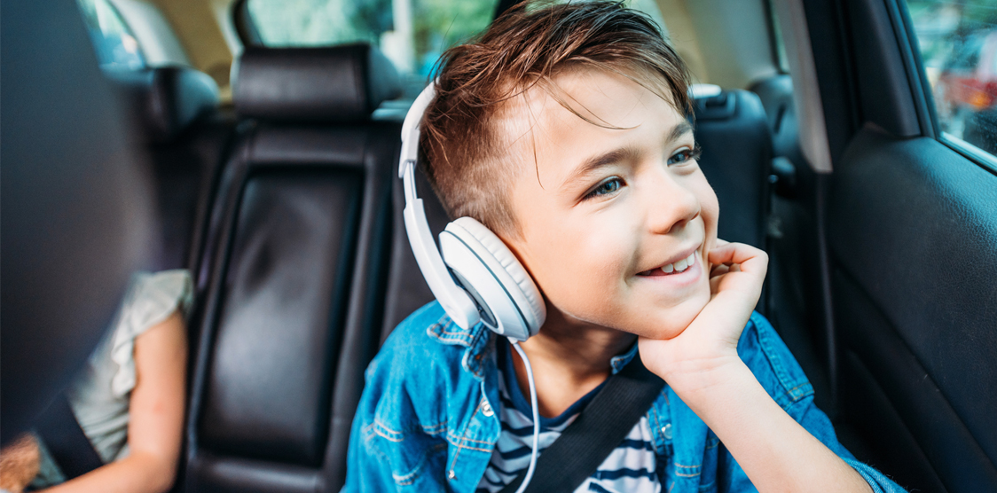 Boy listening to a podcast on a roadtrip