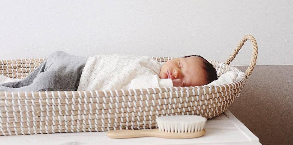 baby sleeping in an Olli Ella changing basket