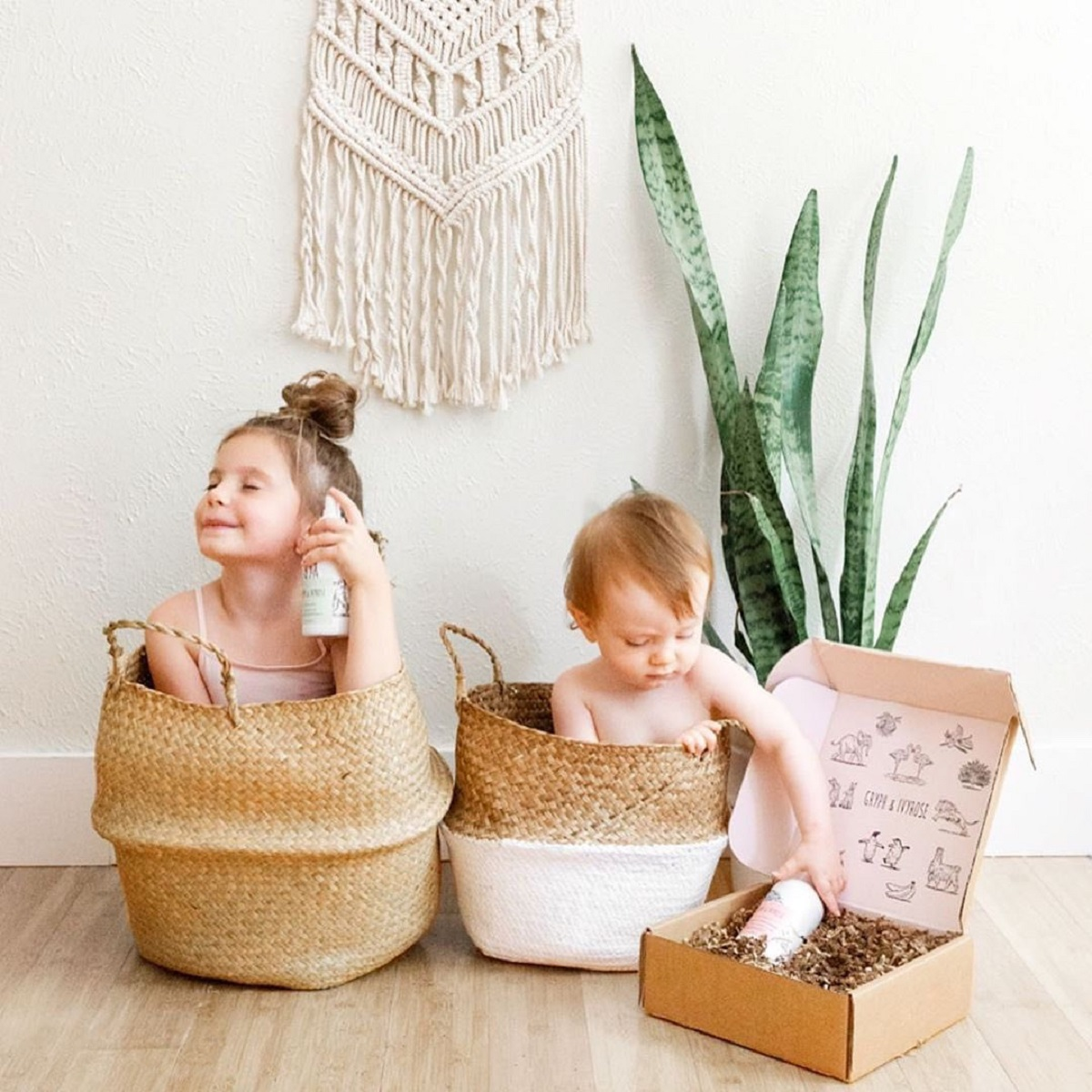 Two Children in baskets with a box of Gryph & Ivyrose products