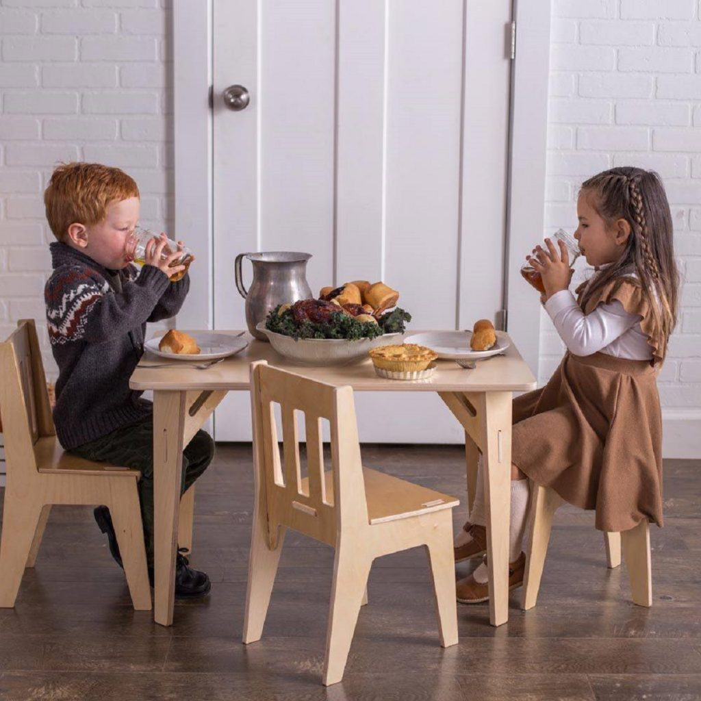 Two children sitting at a Sprout Kids table and chairs