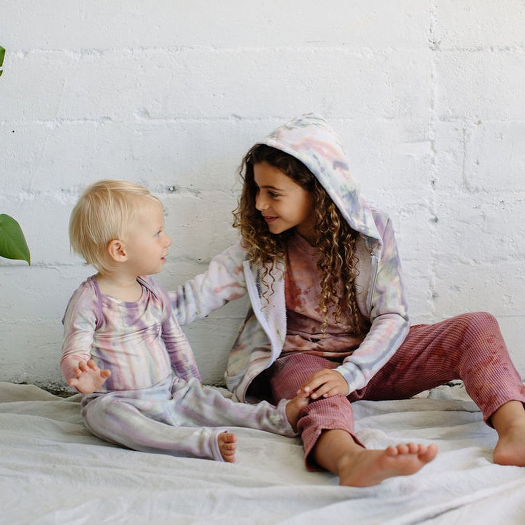 Two chlidren wearing Little Moon Society clothing sitting against a wall