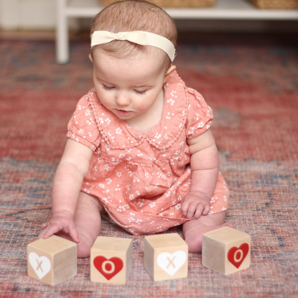 A baby playing with Modern Blocks Valentine's Day XOXO block set