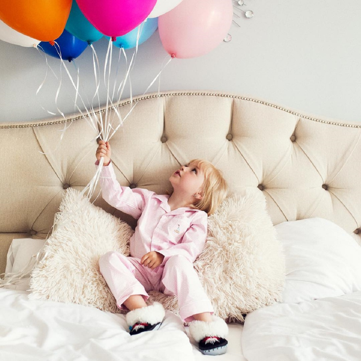 Little girl holding balloons in king sized bed