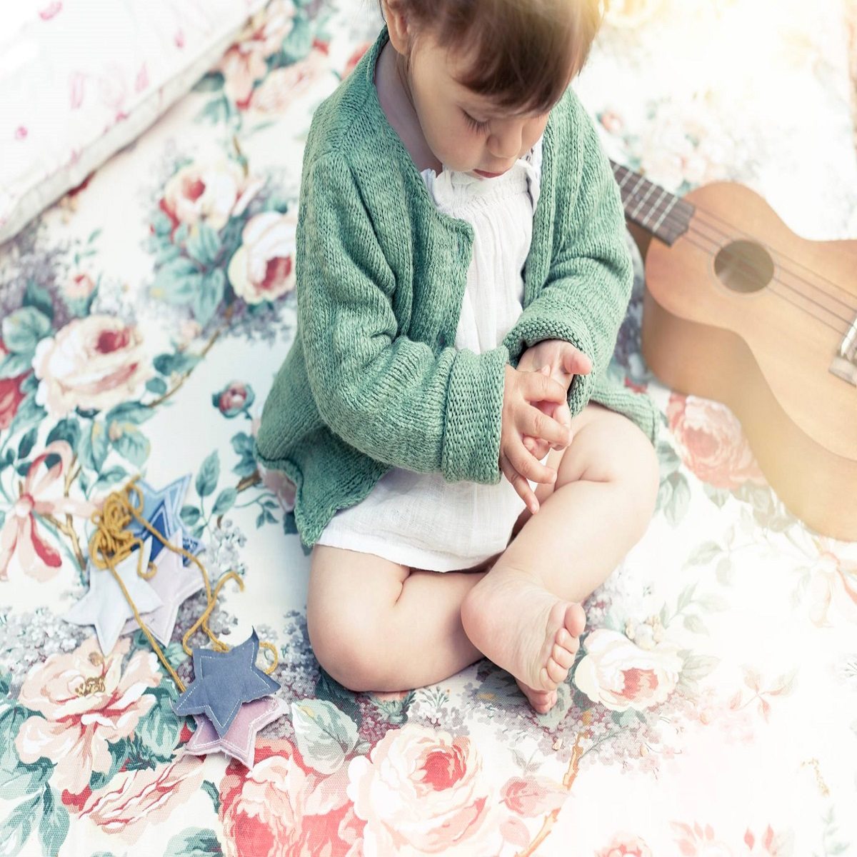 Child sitting on a blanket next to a guitar wearing Tocoto Vintage clothing