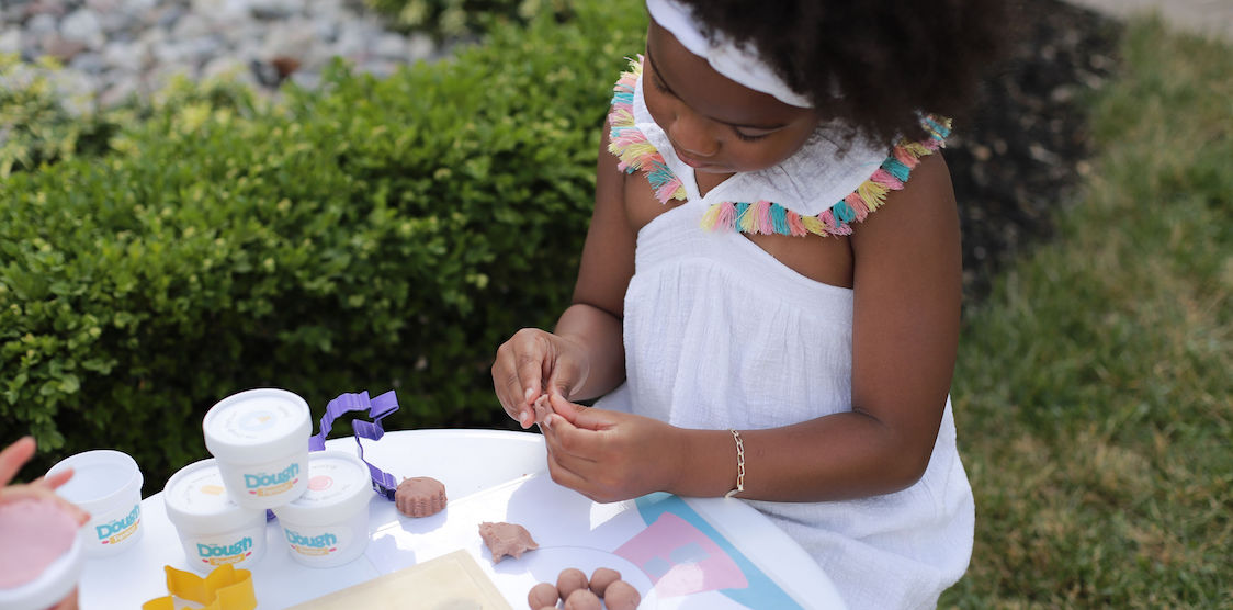 A little girl playing with dough parlour non toxic play dough