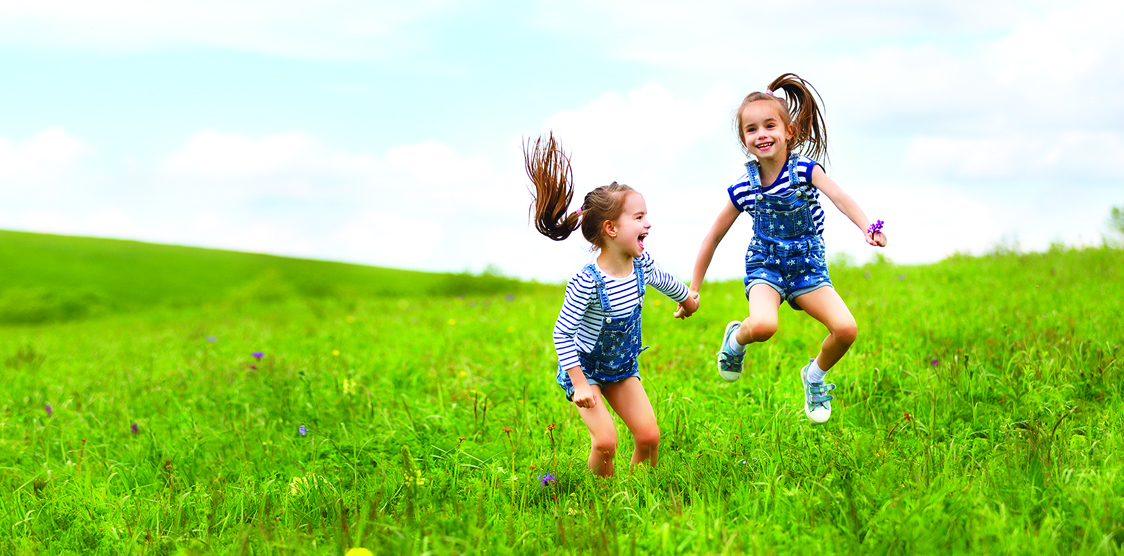twin girls playing in a field