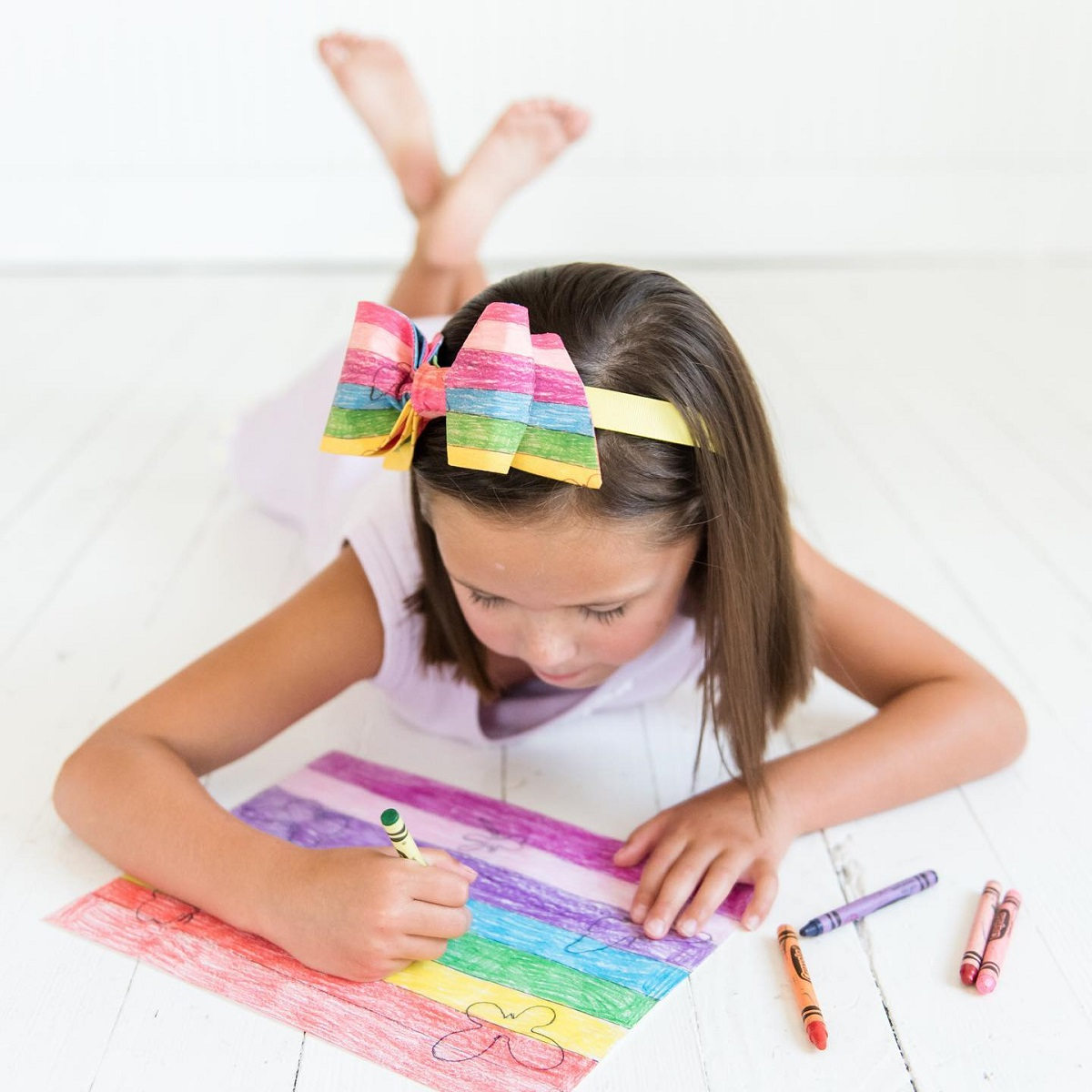 Girl coloring and wearing a Bow Next Door rainbow bow in her hair