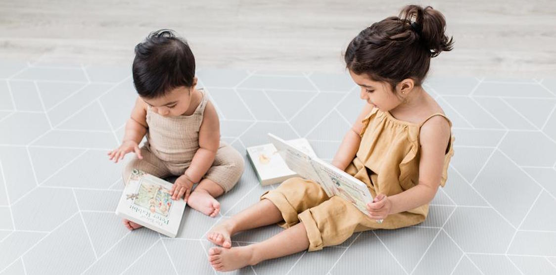 Two kids playing on a Little Bot playmat