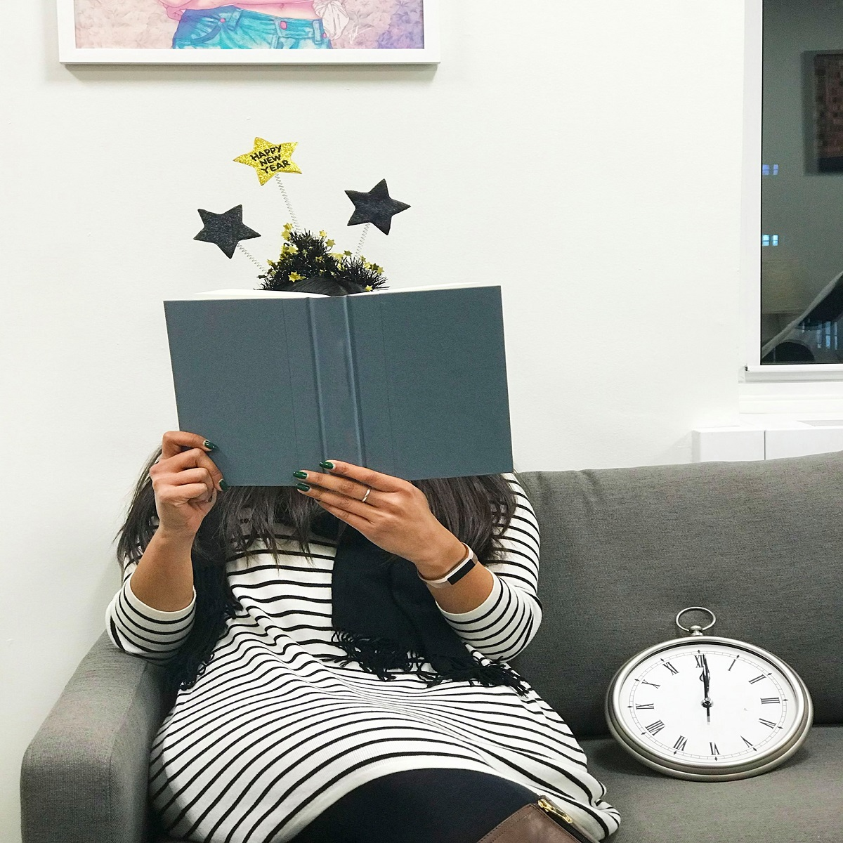 Woman sitting on a couch reading a book on New Years Eve