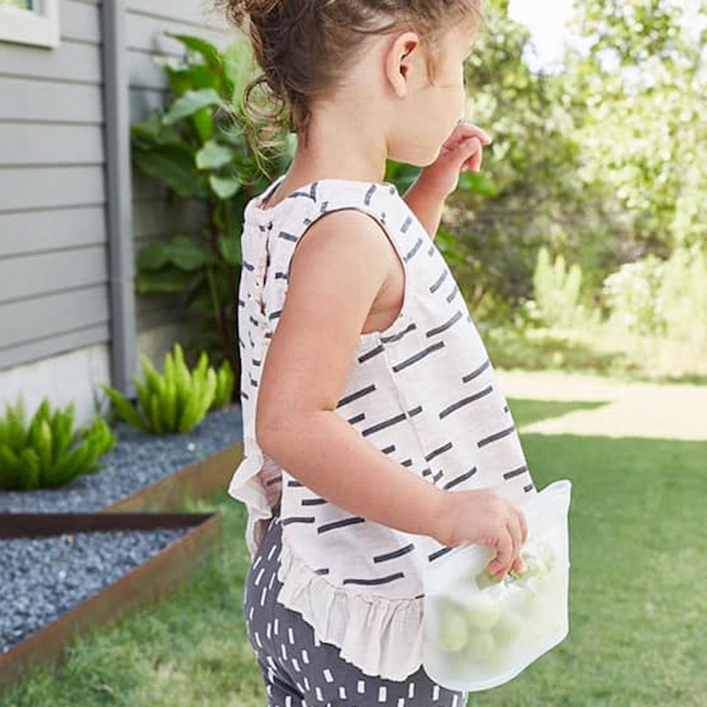 Young girl standing in backyard eating snack from a Zip Top container