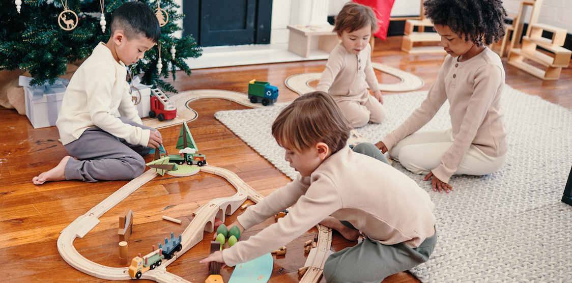 Three kids playing with wooden toys on Christmas morning