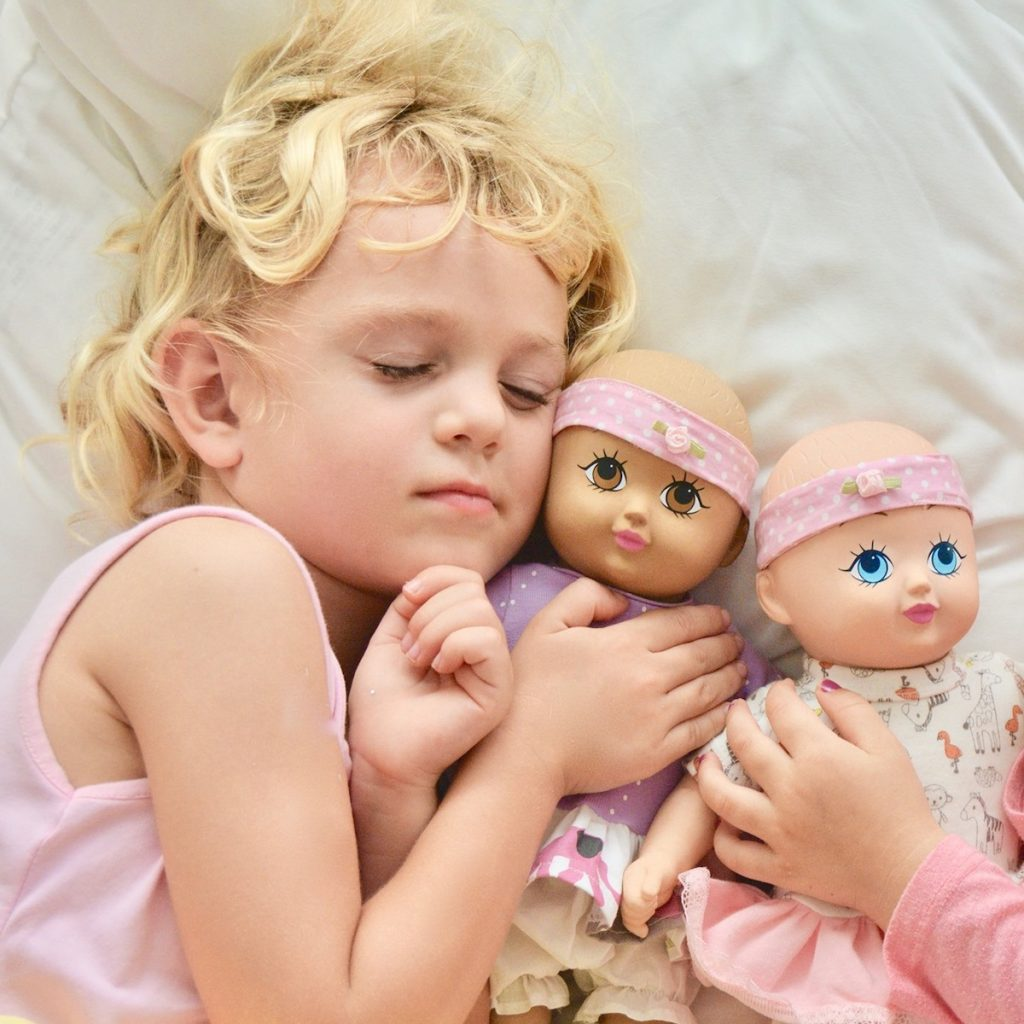 A little girl cuddling her two EcoBaby Dolls