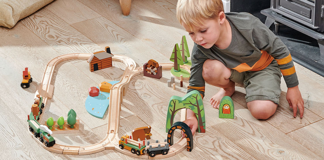 A Blonde Haired Boy playing with the Tender Leaf Toys Wild Pines Train Set