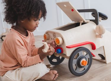 A child playing with the plantoys motor mechanic toy