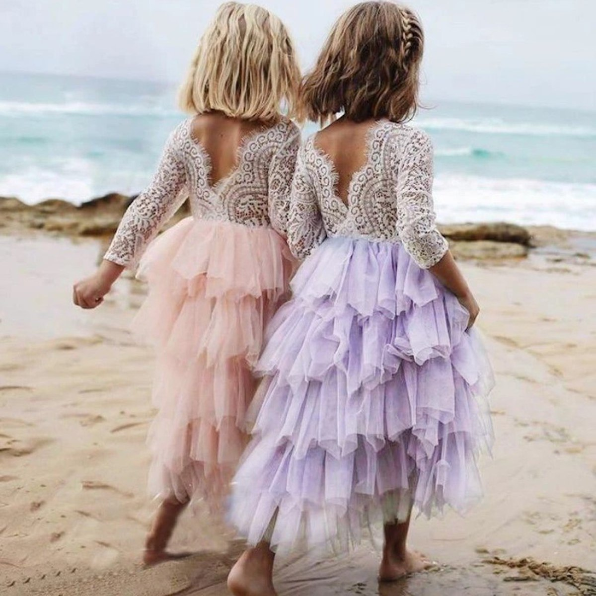 two young girls walking on the beach wearing pink and puple skirts