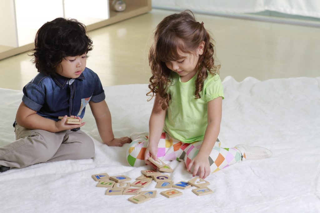 Two kids playing with PlanToys A-Z Alphabet tiles