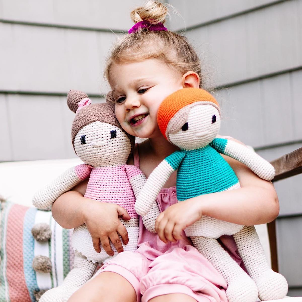 Little girl holding two hand-knit Cuddoll dolls