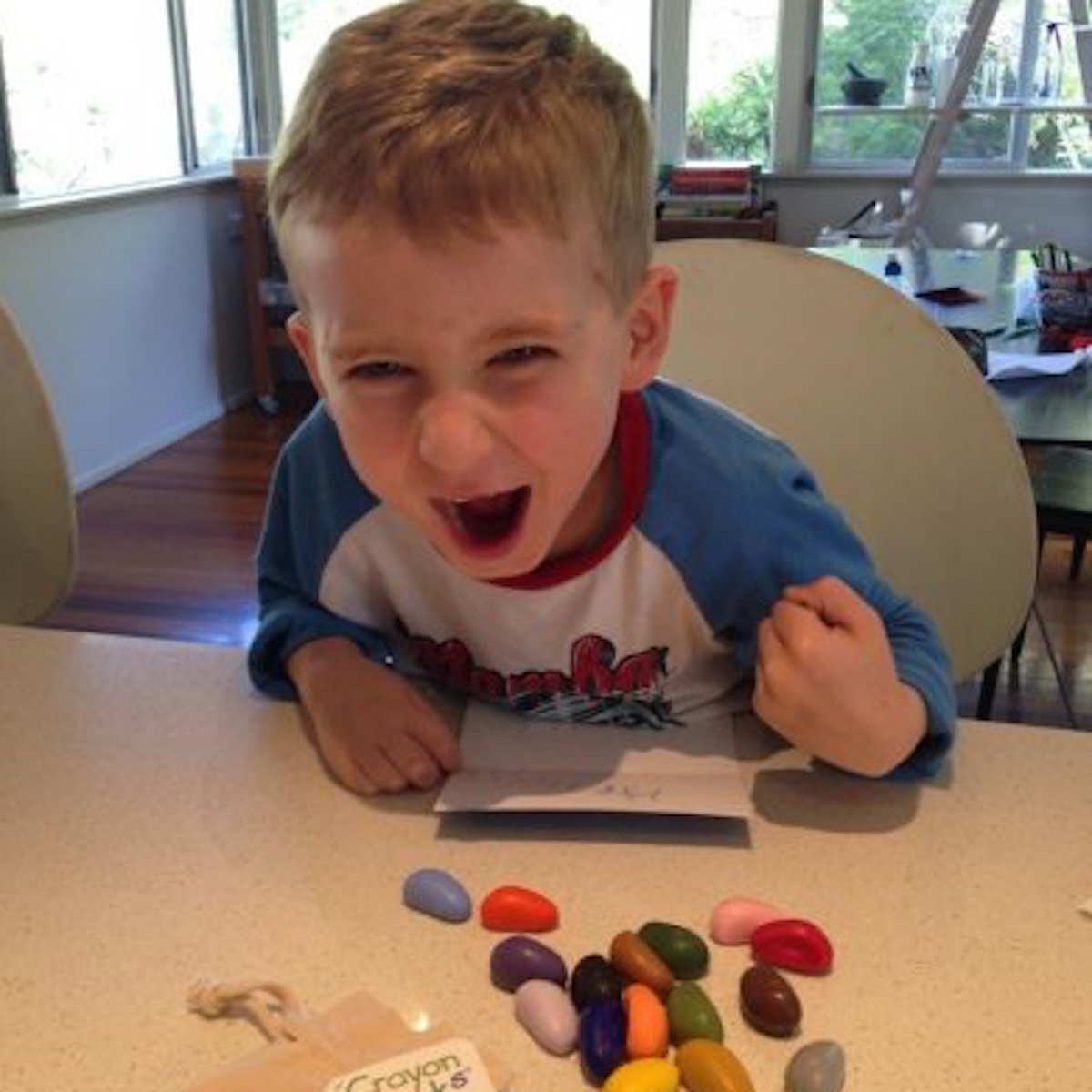 Child coloring with Crayon Rocks at a kitchen table