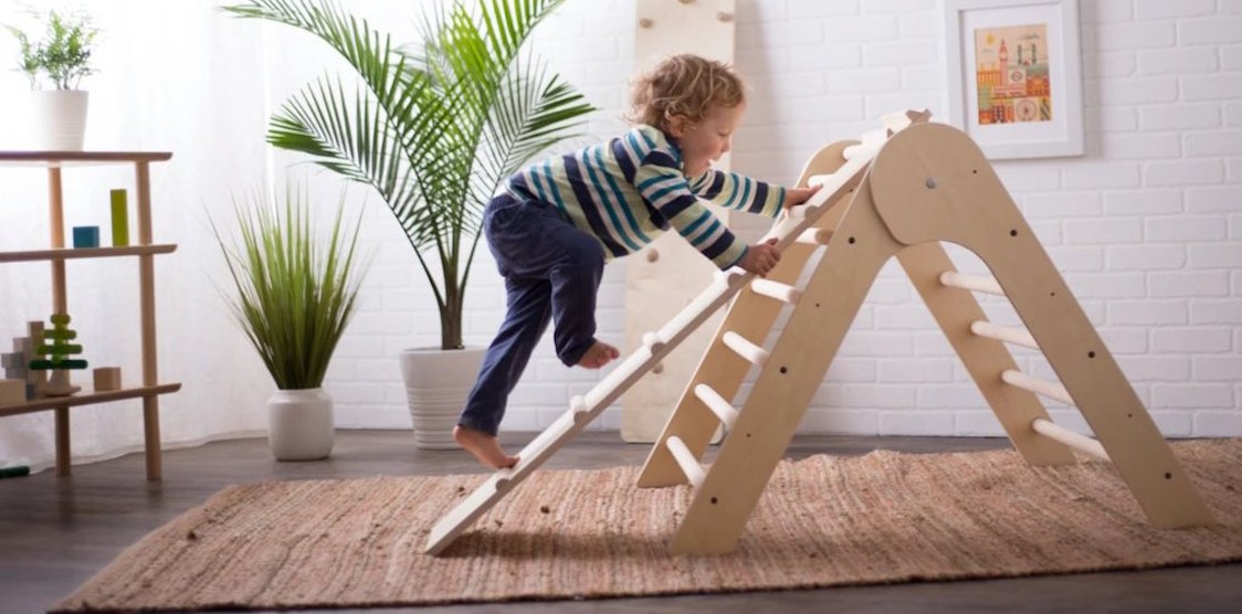 A child playing on the Sprout Triangular Climbing frame with ramp