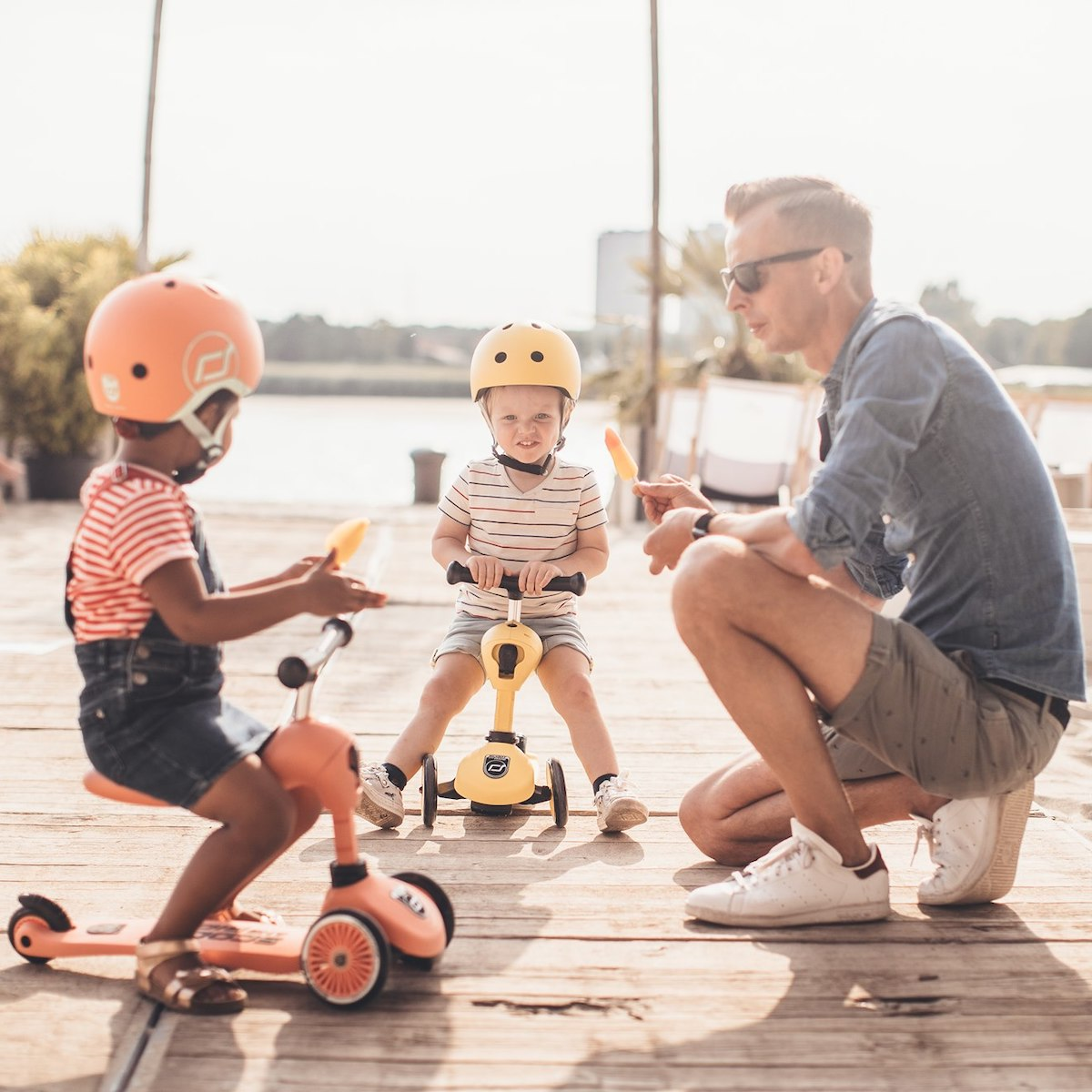 Father and his two children riding scoot & ride scooters on a boardwalk