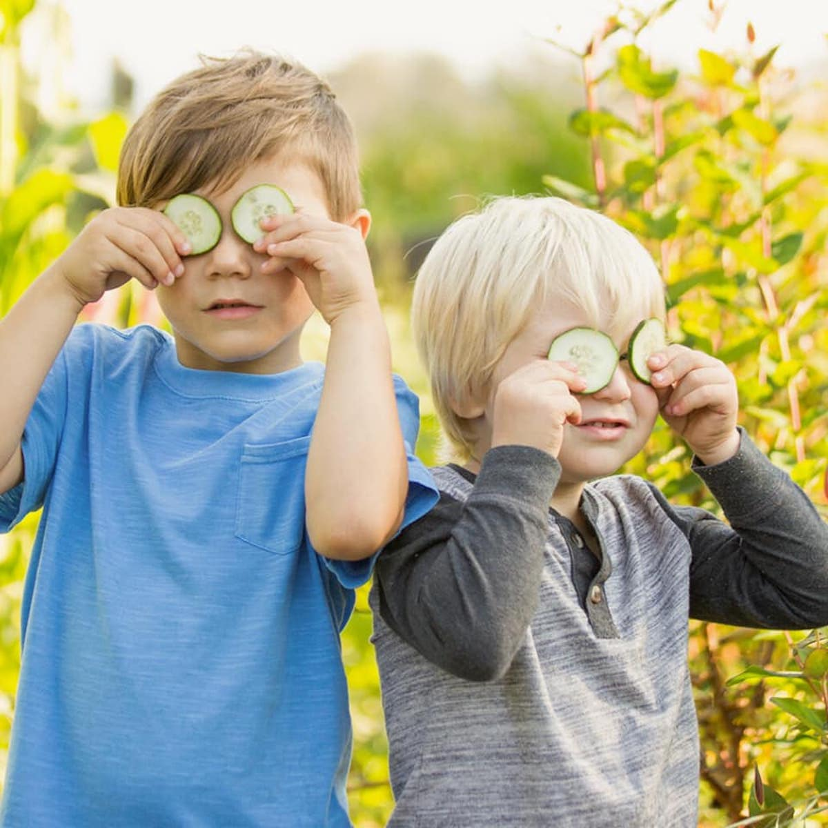 Two childen in a field with cucumbers over their eyes