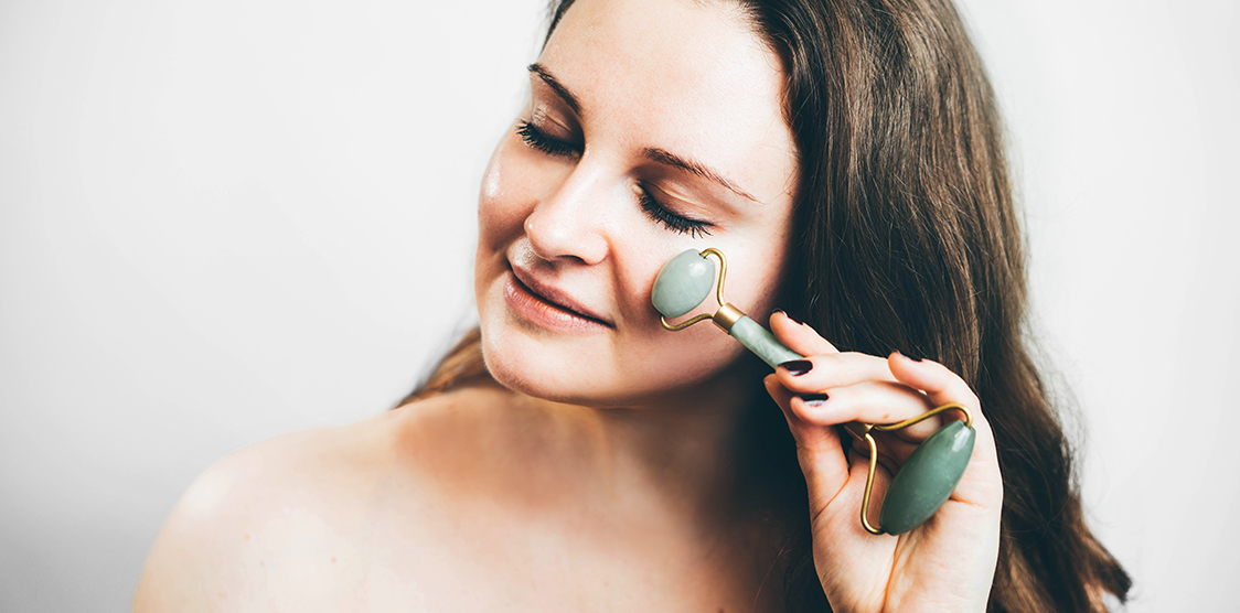Woman using jade roller on her face