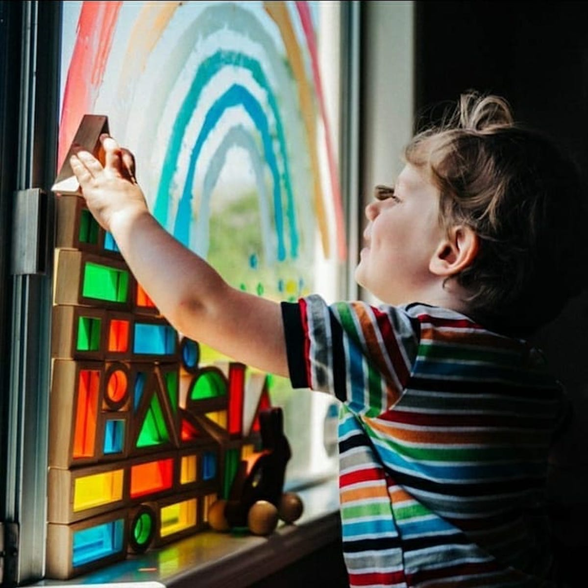 A child playing with Guidecraft Rainbow Blocks by a window