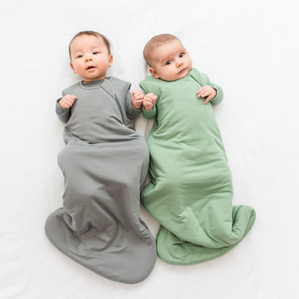 Two babies wearing Kyte Baby Sleeping Bags